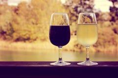 Αναδρομική εικόνα ύφους φίλτρων ηλιοβασιλέματος δύο ποτηριών του κρασιού, άσπρος και κόκκινος, στην ξύλινη ράγα Στοκ Φωτογραφία