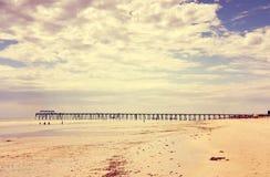 Αναδρομική εκλεκτής ποιότητας στιγμιαία ευρεία ανοικτή παραλία φίλτρων με τον όμορφο ουρανό σύννεφων Στοκ φωτογραφίες με δικαίωμα ελεύθερης χρήσης