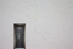 Αναδρομική μεταλλική πόρτα σε έναν ελαφρύ επικονιασμένο τοίχο Στοκ εικόνες με δικαίωμα ελεύθερης χρήσης