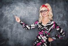 Αναδρομικός δάσκαλος στα γυαλιά που παρουσιάζουν σε κάτι από το δάχτυλο Στοκ Φωτογραφία