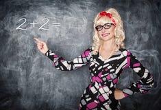 Αναδρομικός δάσκαλος στα γυαλιά που παρουσιάζουν στην εξίσωση από το δάχτυλο Στοκ φωτογραφία με δικαίωμα ελεύθερης χρήσης