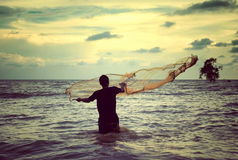 Αναδρομικός φανείτε εικόνα ενός ατόμου που ρίχνει το δίχτυ του ψαρέματος Στοκ Εικόνες