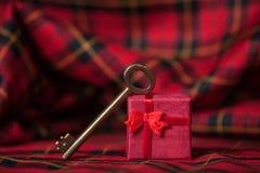 Αναδρομικό βασικό και λίγο κόκκινο δώρο σε ένα τραπεζομάντιλο. Στοκ Εικόνα