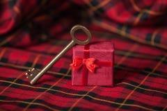 Αναδρομικό βασικό και λίγο κόκκινο δώρο σε ένα τραπεζομάντιλο. Στοκ Εικόνες