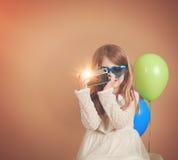 Αναδρομικό εκλεκτής ποιότητας παιδί που παίρνει τη φωτογραφία με την παλαιά κάμερα στοκ εικόνα