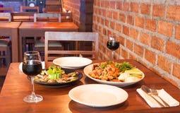 Αναδρομικό εσωτερικό εστιατορίων με τα ταϊλανδικά τρόφιμα και το κόκκινο κρασί Στοκ Εικόνες