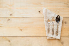 Αναδρομικό κουτάλι στη τοπ άποψη υφασμάτων λινού σχετικά με το ξύλινο υπόβαθρο Στοκ Εικόνες