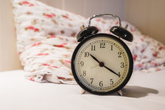 Αναδρομικό ξυπνητήρι με το ρολόι 10 Ο ` και το μενουέτο είκοσι, στο άσπρο κρεβάτι με το μαξιλάρι Στοκ Εικόνες