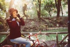 Αναδρομικό οδηγώντας ποδήλατο κοριτσιών μόδας στο πάρκο την ημέρα πτώσης στοκ εικόνες