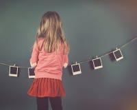 Αναδρομικό παιδί που κρεμά την εκλεκτής ποιότητας ταινία φωτογραφιών στον τοίχο στοκ εικόνες