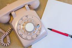Αναδρομικό περιστροφικό τηλέφωνο με το κενό έγγραφο Στοκ Φωτογραφία