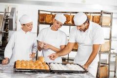 Αναλύοντας ψωμιά Baker στον πίνακα στο αρτοποιείο Στοκ εικόνα με δικαίωμα ελεύθερης χρήσης