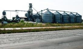 Ανελκυστήρας για την αποθήκευση σιταριού Αποθήκη εμπορευμάτων σιταριού Γεωργικός σύνθετος πίσω από το δρόμο ασφάλτου στοκ εικόνα