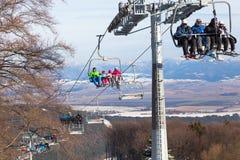 Ανελκυστήρας εδρών με τους σκιέρ τα βουνά υποβάθρου Σλοβακία Στοκ Φωτογραφία