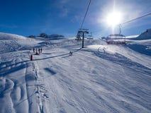 Ανελκυστήρας με τα καθίσματα που πηγαίνουν πέρα από το βουνό και τις πορείες από τους ουρανούς και τα σνόουμπορντ Γαλλία, Meribel Στοκ Εικόνες