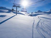Ανελκυστήρας με τα καθίσματα που πηγαίνουν πέρα από το βουνό και τις πορείες από τους ουρανούς και τα σνόουμπορντ Γαλλία, Meribel Στοκ φωτογραφίες με δικαίωμα ελεύθερης χρήσης
