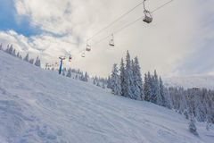 Ανελκυστήρας με τα καθίσματα που πηγαίνουν πέρα από το βουνό και τις πορείες από τους ουρανούς Στοκ φωτογραφίες με δικαίωμα ελεύθερης χρήσης