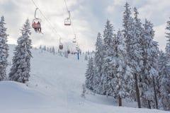 Ανελκυστήρας με τα καθίσματα που πηγαίνουν πέρα από το βουνό και τις πορείες από τους ουρανούς Στοκ Φωτογραφίες