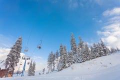 Ανελκυστήρας με τα καθίσματα που πηγαίνουν πέρα από το βουνό και τις πορείες από τους ουρανούς Στοκ Φωτογραφία