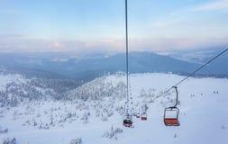 Ανελκυστήρας με τα καθίσματα που πηγαίνουν πέρα από το βουνό και τις πορείες από τους ουρανούς Στοκ εικόνα με δικαίωμα ελεύθερης χρήσης