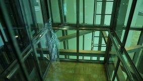 Ανελκυστήρας που κινείται προς τα πάνω και που φθάνει στο πάτωμα, άποψη μέσω του άξονα ανελκυστήρων γυαλιού απόθεμα βίντεο