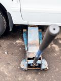 Ανελκυστήρες υδραυλικών γρύλων ένα αυτοκίνητο υπαίθρια στοκ εικόνα με δικαίωμα ελεύθερης χρήσης