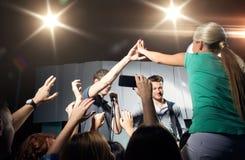 Ανεμιστήρας που κάνει υψηλά πέντε με τον τραγουδιστή στη συναυλία λεσχών στοκ φωτογραφία με δικαίωμα ελεύθερης χρήσης