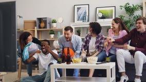 Ανεμιστήρες καλαθοσφαίρισης που προσέχουν το αθλητικό παιχνίδι στη TV που υποστηρίζει στο σπίτι την αγαπημένη ομάδα απόθεμα βίντεο