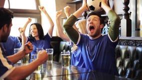 Ανεμιστήρες ποδοσφαίρου που προσέχουν τον αγώνα ποδοσφαίρου στο φραγμό ή το μπαρ απόθεμα βίντεο