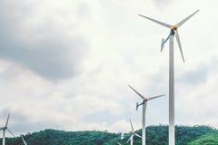 Ανεμοστρόβιλοι για να παραγάγει την ηλεκτρική ενέργεια για τη ανανεώσιμη ενέργεια στο βουνό και το νεφελώδη ουρανό Στοκ Φωτογραφία