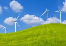 Ανεμοστρόβιλοι που παράγουν την ηλεκτρική ενέργεια στο λιβάδι και το μπλε ουρανό λόφων χλόης Στοκ Φωτογραφίες