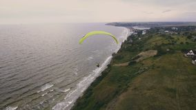 Ανεμόπτερο στον εναέριο πυροβολισμό αέρα Μύγες ατόμων σε ένα ανεμόπτερο πέρα από έναν απότομο βράχο ζωή απόθεμα βίντεο