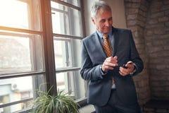 Ανεξάρτητος ανώτερος επιχειρηματίας στο κοστούμι με το smartphone Στοκ φωτογραφία με δικαίωμα ελεύθερης χρήσης