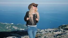 Ανεξάρτητος ελκυστικός θηλυκός τουρίστας στο καπέλο κάουμποϋ και γυαλιά ηλίου που απολαμβάνουν καταπληκτικός τη φύση φιλμ μικρού μήκους
