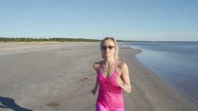 Ανεξάρτητος νέος αθλητής γυναικών που τρέχει στην παραλία που ασκεί το θηλυκό δρομέα που τρέχει γρήγορα την κατάρτιση στο ηλιόλου φιλμ μικρού μήκους