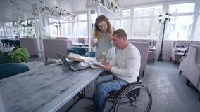 Ανεξάρτητος τρόπος ζωής του άκυρου, δημιουργικού με ειδικές ανάγκες ατόμου στην αναπηρική καρέκλα με το θηλυκό με τον καφέ φλυτζα απόθεμα βίντεο