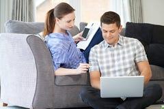 Ανεξάρτητο ζεύγος που εργάζεται από το σπίτι που εξετάζει το lap-top από κοινού Στοκ φωτογραφία με δικαίωμα ελεύθερης χρήσης