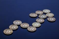 Ανερχόμενος βέλος από τα χρυσά bitcoins στο μπλε υπόβαθρο Στοκ εικόνα με δικαίωμα ελεύθερης χρήσης