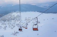 Ανελκυστήρας με τα καθίσματα που πηγαίνουν πέρα από το βουνό και τις πορείες από τους ουρανούς Στοκ Εικόνες