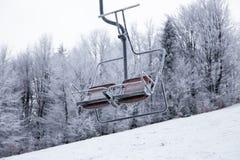 Ανελκυστήρας με τα καθίσματα που πηγαίνουν πέρα από το βουνό και τις πορείες από τους ουρανούς Στοκ εικόνες με δικαίωμα ελεύθερης χρήσης