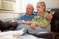 Ανησυχημένη ανώτερη συνεδρίαση ζεύγους στον καναπέ που εξετάζει Bill στοκ φωτογραφίες