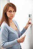 Ανησυχημένη γυναίκα με τη θέρμανση του Μπιλ που γυρίζει κάτω τη θερμοστάτη Στοκ Φωτογραφίες