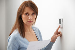Ανησυχημένη γυναίκα με τη θέρμανση του Μπιλ που γυρίζει κάτω τη θερμοστάτη στοκ εικόνες