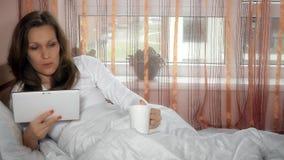 Ανησυχημένη γυναίκα που διαβάζει τις κακές ειδήσεις στον υπολογιστή ταμπλετών και το τσάι καφέ πρωινού ποτών φιλμ μικρού μήκους