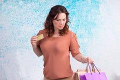 Ανησυχημένη γυναίκα που κρατά τις ζωηρόχρωμες τσάντες εγγράφου αγορών, που καταθέτουν σε τράπεζα cre Στοκ εικόνα με δικαίωμα ελεύθερης χρήσης