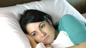 Ανησυχημένη γυναίκα στο κρεβάτι απόθεμα βίντεο