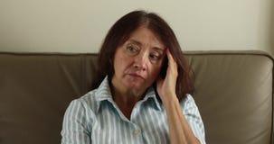 Ανησυχημένη ενήλικη γυναίκα που τρίβει το ναό φιλμ μικρού μήκους