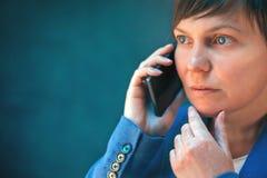 Ανησυχημένη επιχειρηματίας που μιλά στο κινητό τηλέφωνο Στοκ Φωτογραφία