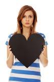 Ανησυχημένη εφηβική γυναίκα που κρατά τη μαύρη καρδιά εγγράφου Στοκ Φωτογραφίες