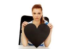 Ανησυχημένη εφηβική γυναίκα που κρατά τη μαύρη καρδιά εγγράφου Στοκ Φωτογραφία